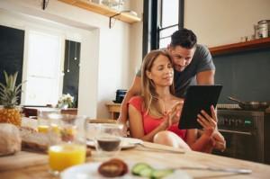 Ein Paar sitzt in der Küche am Frühstückstisch und schaut auf ein Tablet